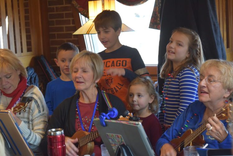 Oh what fun it is to play with any kind of ukulele.  Susie Fouts, a member of TRU Ukes, gets a little backing from her grandchildren during the group's December meeting at Pizza Hut Coventry.  (Photo by Lisa M. Esquivel Long of The News-Sentinel)
