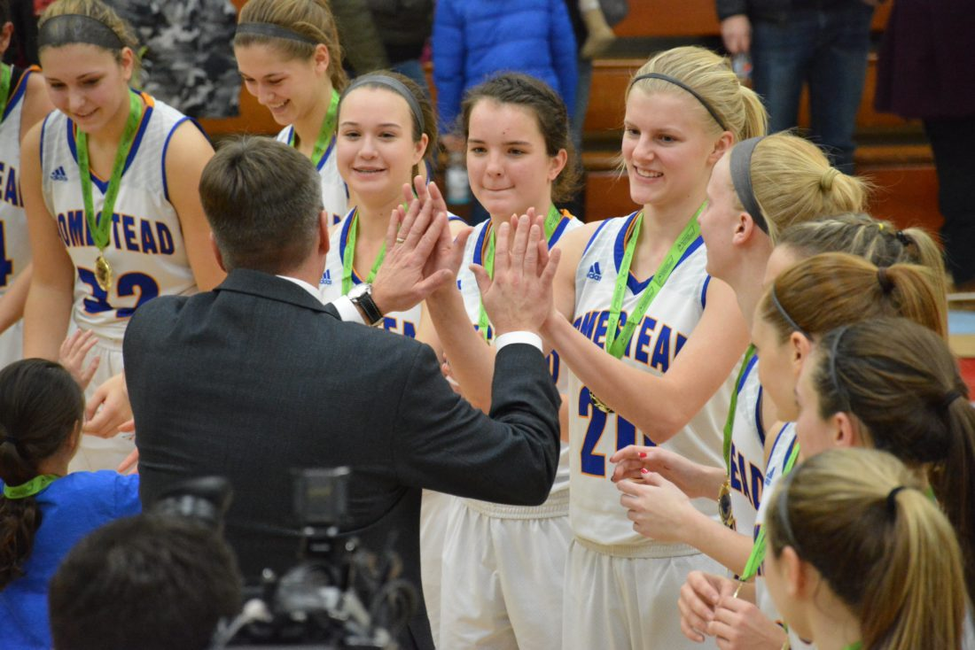 Homestead girls basketball coach Rod Parker high-fives Lauren Selking after the Spartans won their second straight SAC Holiday Tournament on December 29, 2016 at Wayne High School. Visible to Selking's right are teammates Rylie Norton, Rylee Parker, Haley Swing and Sydney Graber. (Photo by Dan Vance of The News-Sentinel)