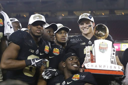 Purdue quarterback Elijah Sindelar, top right, holds the trophy next to teammates after their 38-35 win over Arizona during the Foster Farms Bowl football game Wednesday in Santa Clara, Calif. (Photo by the Associated Press)