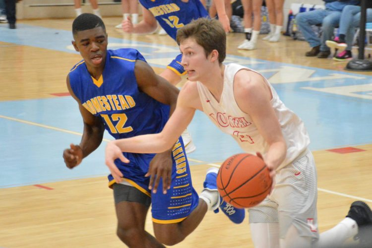 North Side senior Austin Boucher brings the ball up the court against the defense of Homestead's Onye Ezeakudo during Friday's semifinal game at Wayne. (Photo by Dan Vance of news-sentinel.com)