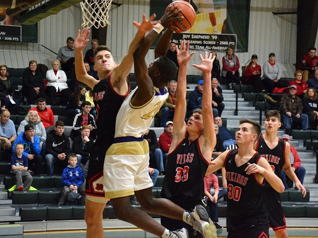 New Haven's Davion Harris tries to score over Huntington North's Hank Pulver, left, during their game Friday at Huntington University. (Photo by Reggie Hayes of news-sentinel.com)