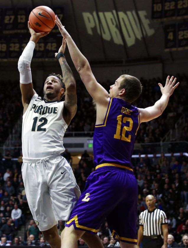Purdue forward Vincent Edwards, left, shoots while defended by Lipscomb forward Matt Rose, right, in the first half of a game Saturday in West Lafayette. (By The Associated Press)