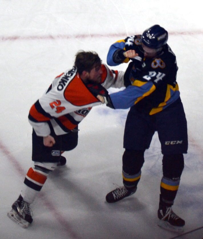 Komets center Dennis Kravchenko tangles with Toledo's Kevin Gibson during the second period.  (By Blake Sebring of News-Sentinel.com)