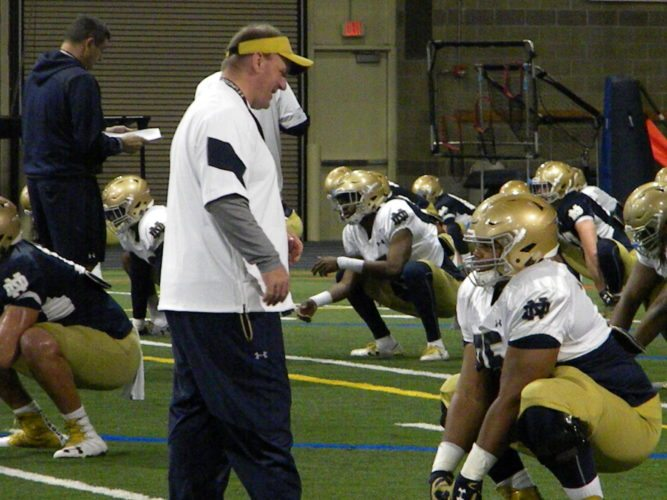 Notre Dame defensive coordinator Mike Elko speaks with a player prior to a practice in spring of last year at the Guglielmino Athletics Complex in South Bend. (By Tom Davis of News-Sentinel.com)