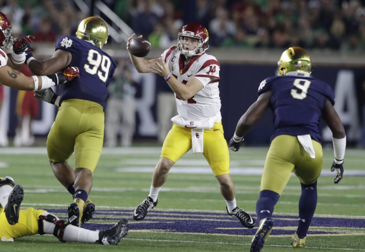 Southern California quarterback Sam Darnold (14) bobbles a high snap before fumbling, while Notre Dame defenders Jerry Tillery (99) and Daelin Hayes (9) pursue him  during the first half of a game this past season in South Bend. (By The Associated Press)