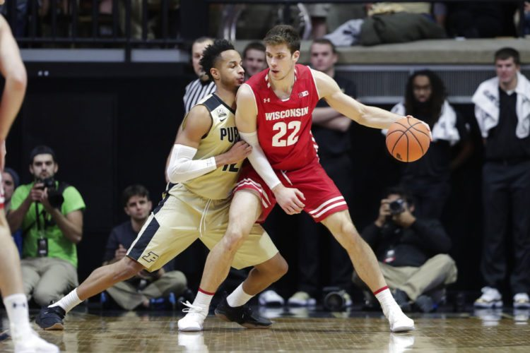 Purdue forward Vincent Edwards (12) defends Wisconsin forward Ethan Happ (22) in the second half of a game in West Lafayette Tuesday. Purdue defeated Wisconsin 78-50. (By The Associated Press)