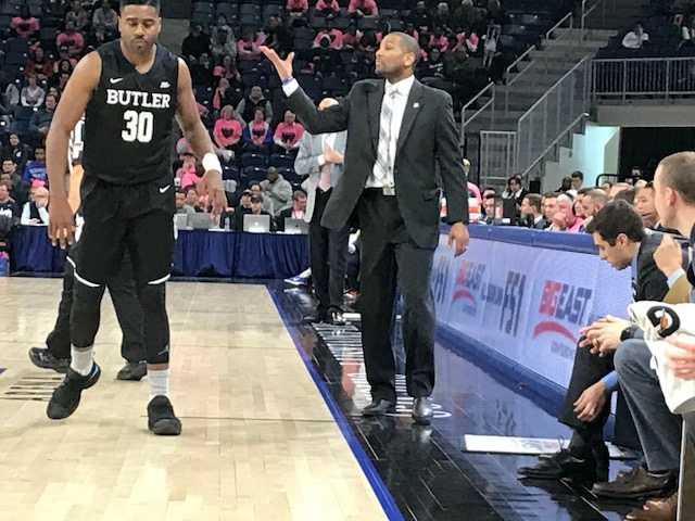 Butler University men's basketball coach LaVall Jordan motions to his team, while senior forward Kelan Martin runs by in a game against DePaul Saturday in Chicago. (By Tom Davis of News-Sentinel.com)