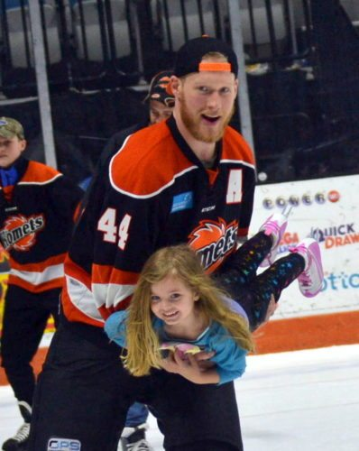 Komets defenseman Cody Sol carries 4 year-old Makayla Willett around the ice during Sunday's post-game skate. (By Blake Sebring of News-Sentinel.com)