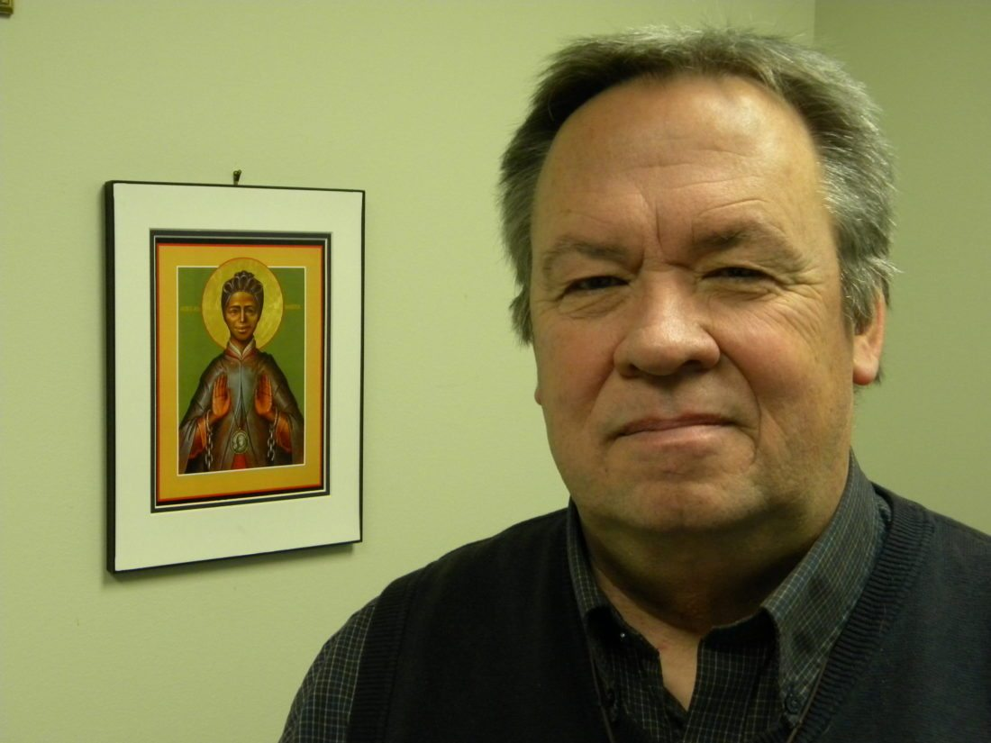 """Bill Duffy, the Josephine's Hope project director at University of Saint Francis, was inspired by the story of St. Josephine Bakhita, background, to work to end human trafficking. Duffy wrote a prayer book, """"Awaited by This Love,"""" that will be used Jan. 30-Feb. 7 at USF as part of activities to pray for an end to human trafficking and to educate people about how to stop it. (By Kevin Kilbane of News-Sentinel.com)"""