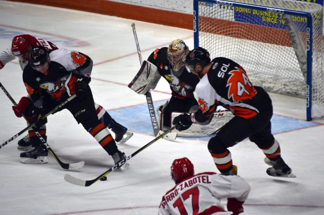 Komets defensemen Jason Binkley, left, and Cody Sol clear the front of the net to protect goaltender Garrett Bartus during Sunday's game against Allen. (By Blake Sebring of News-Sentinel.com)