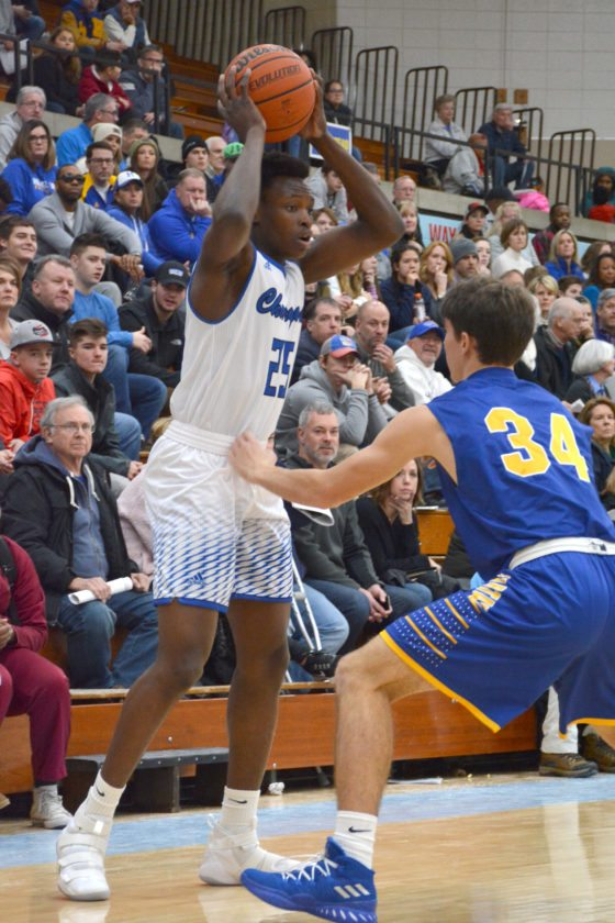 Carroll junior David Ejah looks for a pass over Homestead's Trevin Taylor during this past December's SAC Holiday Tournament. (Photo by Dan Vance of news-sentinel.com)