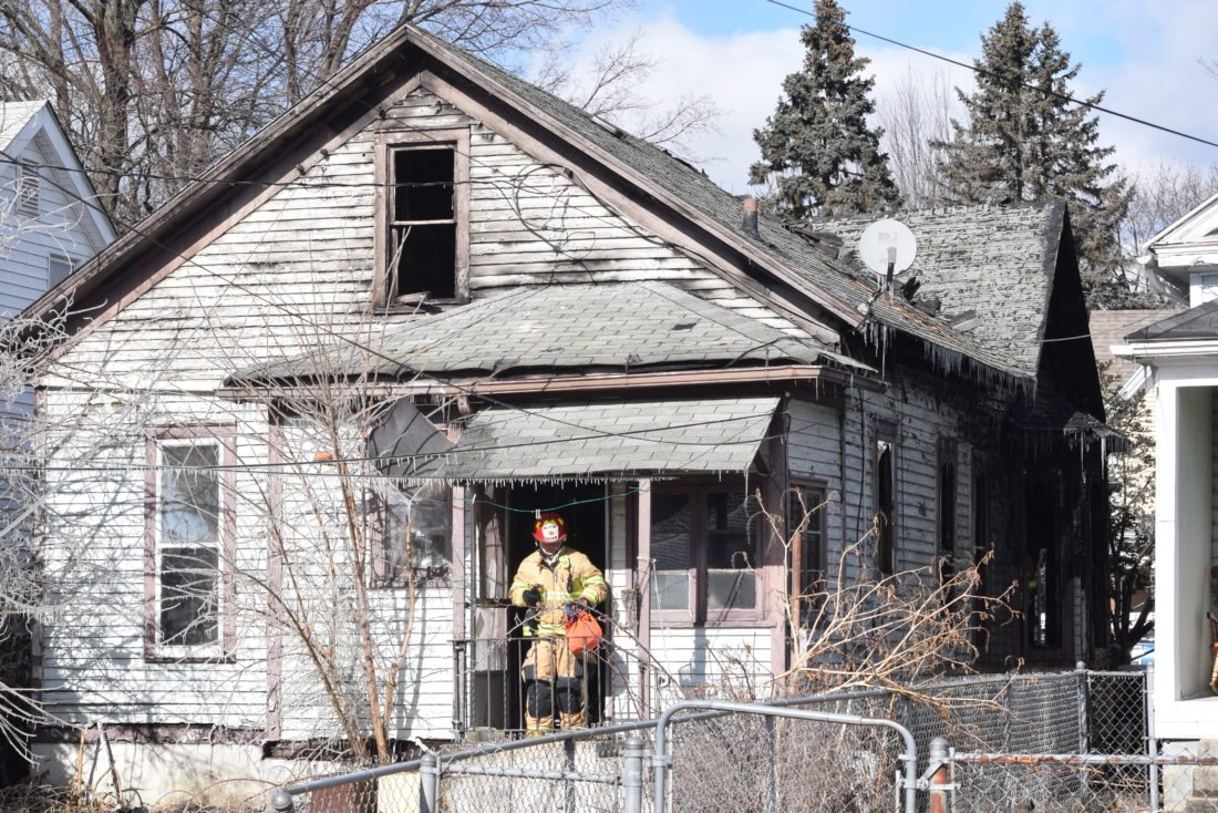 A Fort Wayne firefighter comes out of a Huestis Avenue home on Friday where two people were found  dead during a blaze. (Photo by Lisa M. Esquivel Long of News-Sentinel.com)