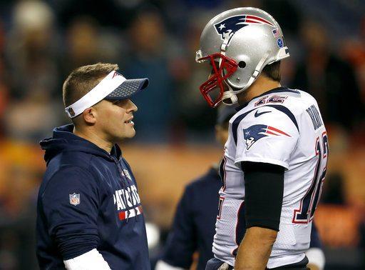 New England Patriots offensive coordinator Josh McDaniels talks with Tom Brady prior to an NFL football game against the Denver Broncos, Sunday, Nov. 12, 2017, in Denver. (AP Photo/David Zalubowski)