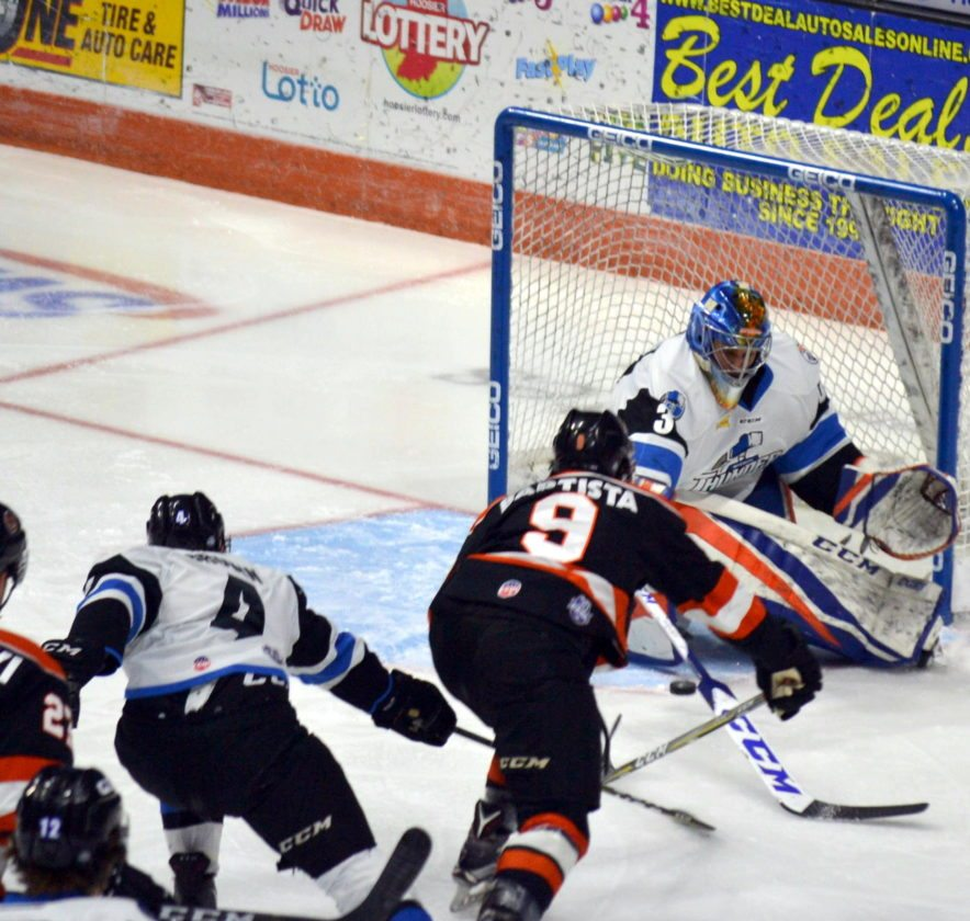 Mason Baptista slides the puck through the pads of Wichita goaltender Shane Starrett on Fort Wayne's first shot of  the game Wednesday night to give the Komets a 1-0 lead. (By Blake Sebring of News-Sentinel.com)