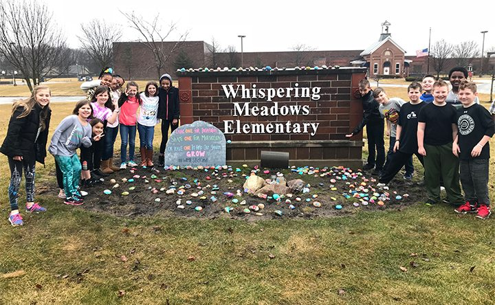 Students from Whispering Meadows Elementary pose for a photo with some of the more than 400 rocks the school's students painted with kind words or an inspirational message. The students set them out by the school sign in hopes people from the community will take them and place where they can be found by another person, spreading kindness throughout Fort Wayne.  (Courtesy of Stacey Fleming of Southwest Allen County Schools)