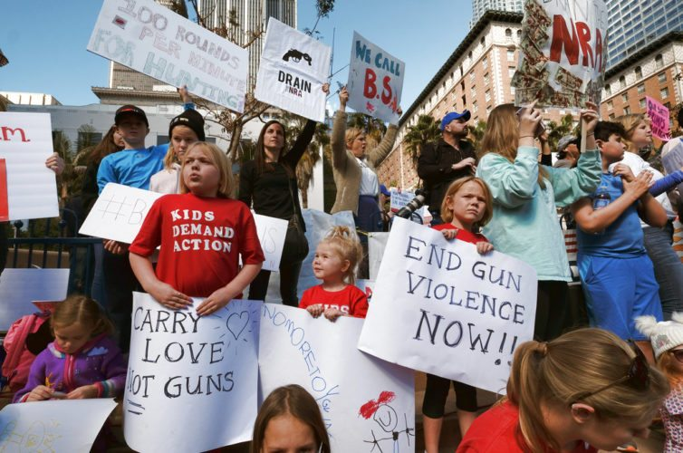 Children join their parents during a protest rally Monday against gun violence in downtown Los Angeles.  Hundreds of sign-carrying, chanting protesters converged on the downtown park to demand tougher background checks and other gun-safety measures following last week's deadly school shooting in Florida. (AP Photo/Richard Vogel)