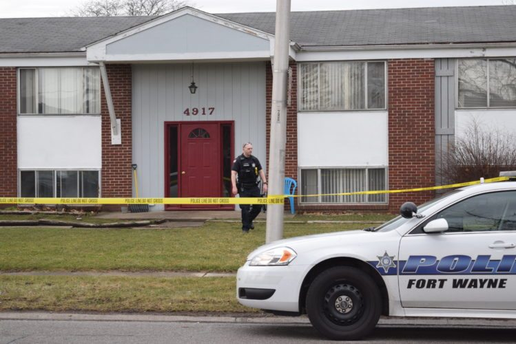 A Fort Wayne Police member walks outside the building where a man was found shot to death Tuesday afternoon. (Photo by Lisa M. Esquivel Long of News-Sentinel.com)