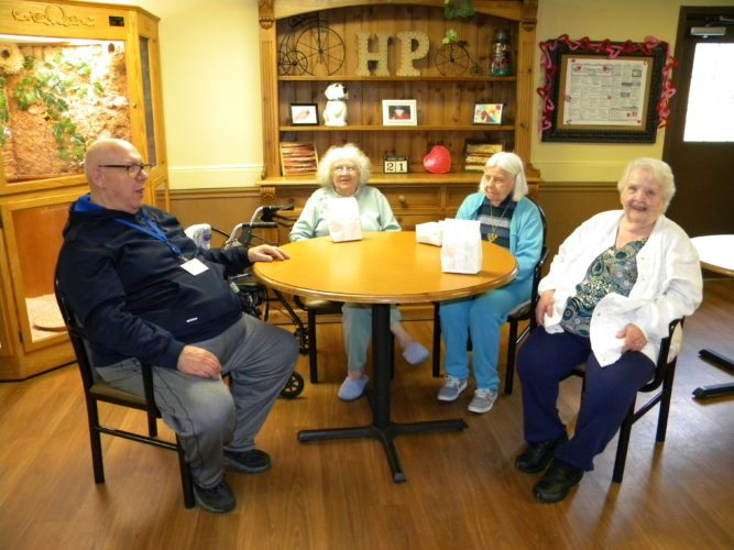 Denny Parker, left, chats with, from left, Marna Bixler, Berneice Newsom and Lois Kaufman at Heritage Park senior health community on Hobson Road. Heritage Park staff recently honored Parker for his volunteer work there, which began while he was a patient there and recovering from major surgery. (By Kevin Kilbane of News-Sentinel.com)
