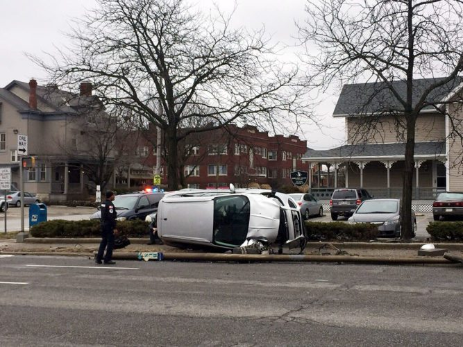A van is on its side Friday afternoon in the park strip on the east side of Lafayette Street after a crash. (Photo by Lisa M. Esquivel Long of News-Sentinel.com)
