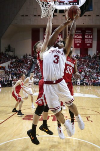 Indiana forward Justin Smith, center, goes to the basket in front of Ohio State center Micah Potter, left, and forward Keita Bates-Diop during the first half of a game in Bloomington Friday. (By The Associated Press)