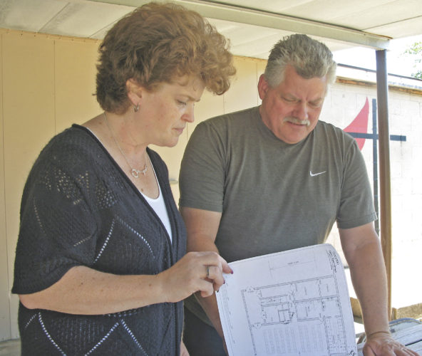 Photo by Jeffrey Saulton Lisa Withee, Crossroads Camp Board of Directors chairperson, left, and Darryl Tucker, camp manager, right, look over drawings for the new lodge at Crossroads United Methodist Church Camp.