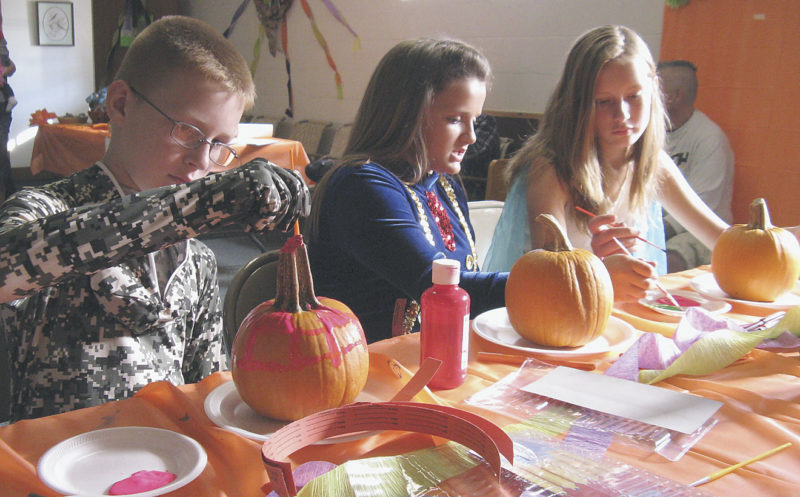 Photo by Jeffrey Saulton Decorating pumpkins at the Lauckport-Park View United Methodist Charge All Saint's Day celebration Saturday were, from left, Charles Hornbeck, Stefania DeMetro and Kaitlyn Hornbeck.