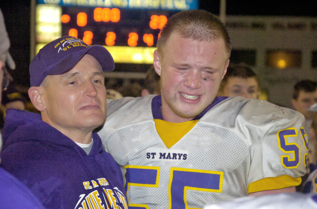 St. Marys' head man Jodi Mote and senior Jacob Northrop share a moment after winning the first state championship in the history of the school.