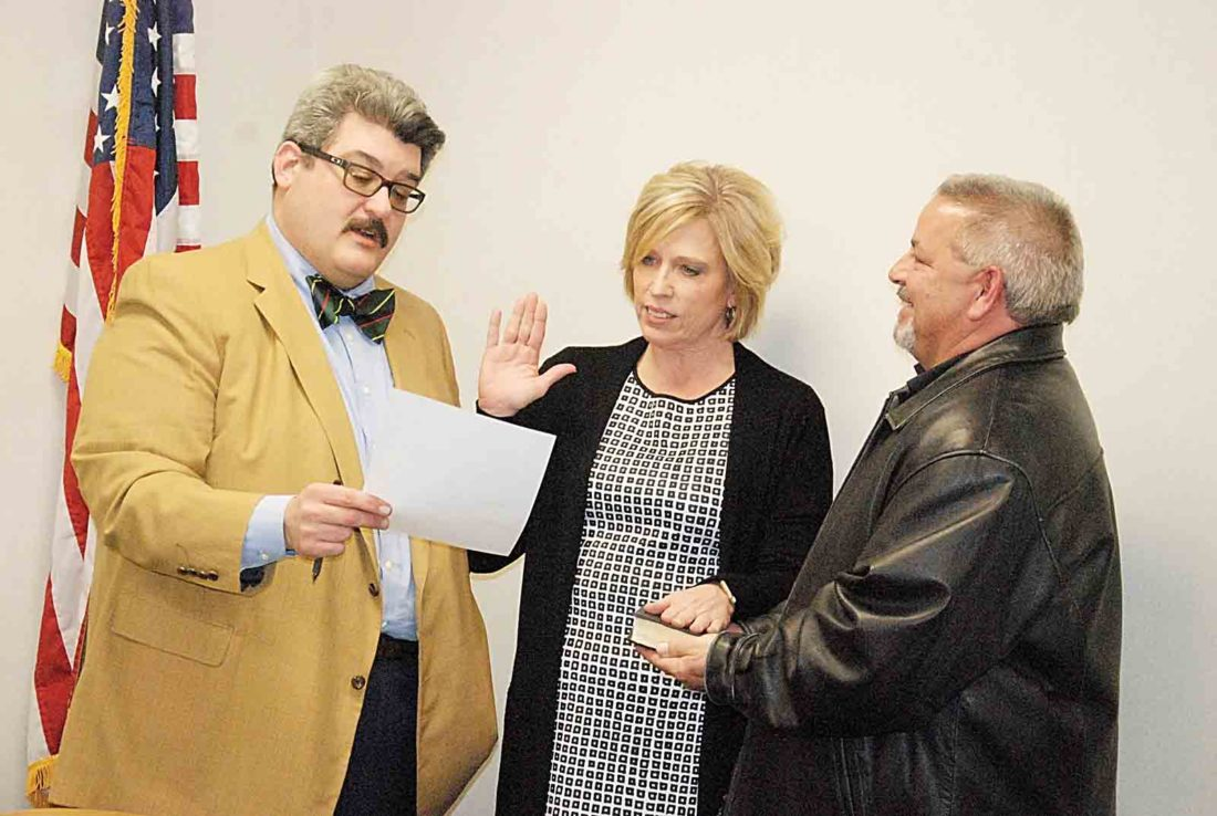 Parkersburg Mayor Tom Joyce, left, administers the oath of office to newly appointed city Personnel Director Sondra Wallace, center, as her husband, Craig, holds the Bible in the small conference room adjacent to council chambers after Tuesday's Parkersburg City Council meeting. Council approved the nomination 7-2. (Photo by Evan Bevins)