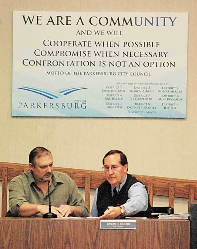 Parkersburg City Council President J.R. Carpenter, left, talks with City Attorney Joe Santer, prior to the start of Tuesday's meeting, in council chambers. Above them is a banner displaying the council's motto, approved during the meeting. (Photo by Evan Bevins)