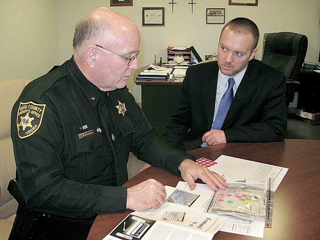 Photo by Jess Mancini From left, Wood County Sheriff Steve Stephens shows Prosecutor Pat Lefebure Fentanyl-laced filing stickers found during a recent investigation. The stickers are placed in the mouth to allow the opioid to enter into the body.