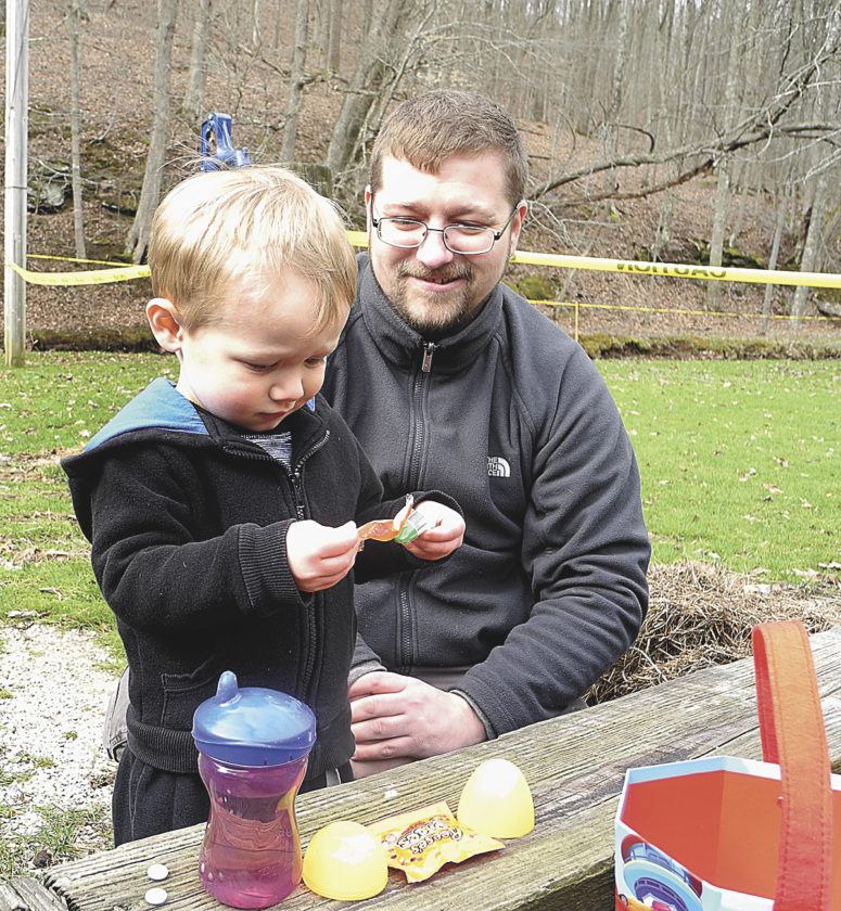File Photo Aiden McCartney, left, of Vienna, shows off the eggs he collected to his dad, Chace McCartney, at last year's Friends of Mountwood Park  Easter Egg Hunt.