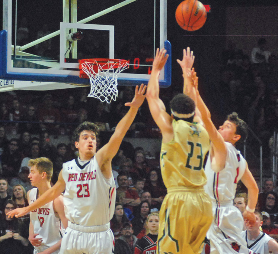 Notre Dame's Jarrod West beats the first quarter buzzer during Saturday's Class A state championship game as Ravenswood's Stephen Dawson (23) and Blake Bennett (4) challenge the shot. West had a game-high 29 points and led the Irish to their first state title via a 63-55 victory against the Red Devils. Photo by Jay W. Bennett.