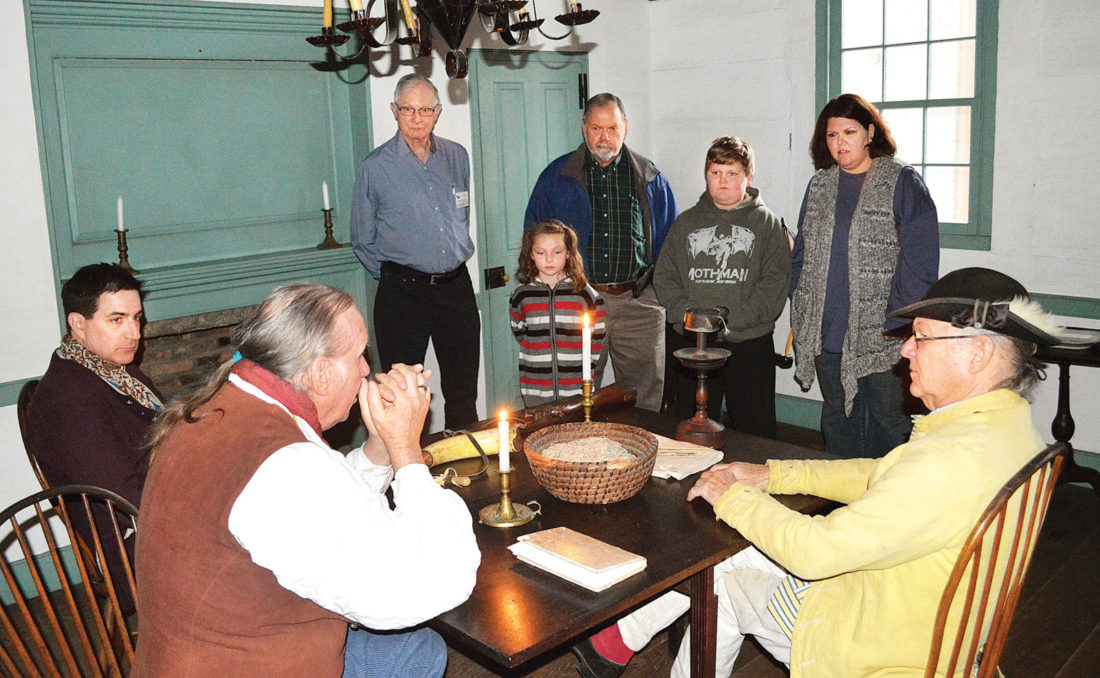 Photo by Doug Loyer A tour guide, Chuck Yonker, Holly Smith and her children enjoy listening to the living historians at Campus Martius Museum on Saturday.
