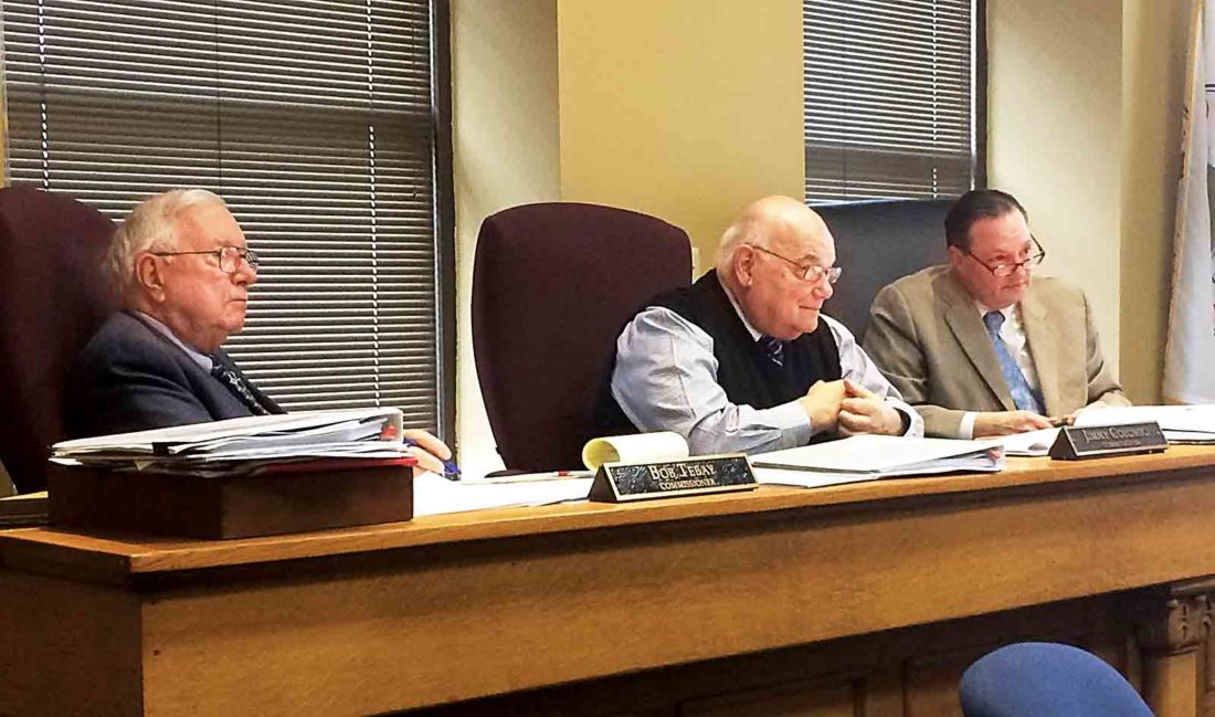 Wood County Commissioners Robert Tebay, Jimmy Colombo and Blair Couch discuss on Monday ways the county can deal with its rising jail bill, including controlling purchases made by county departments. (Photo by Brett Dunlap)