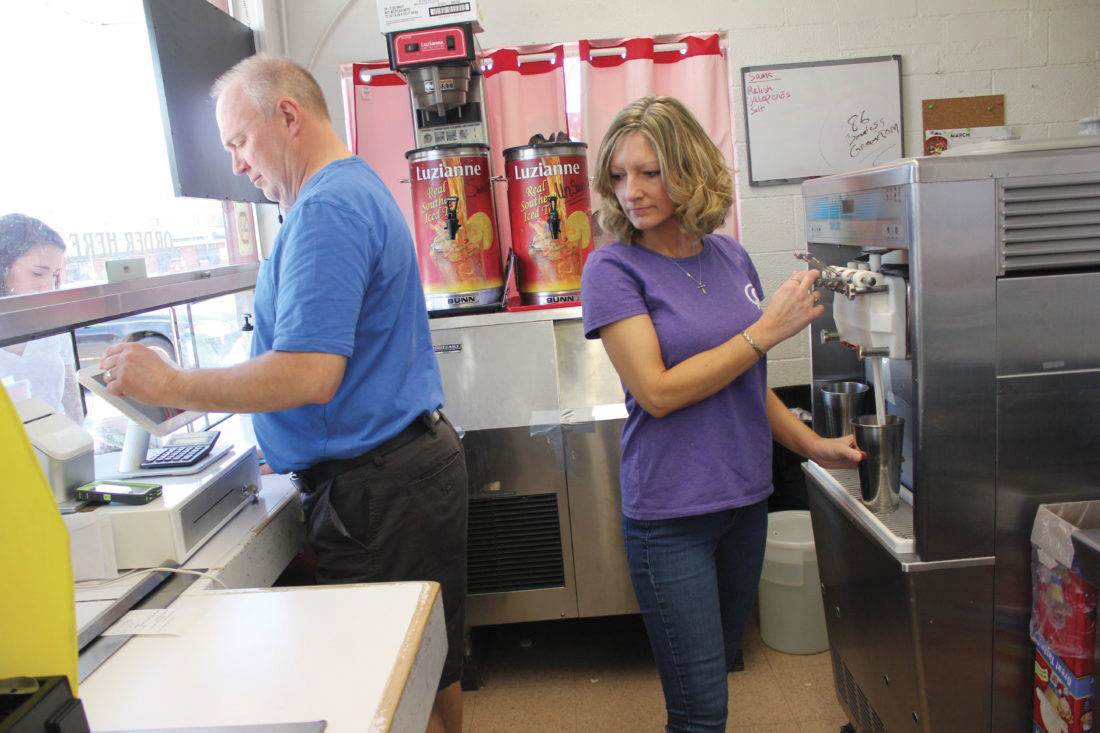 Photo by Janelle Patterson Jeff and Kristina Neader take and fill orders at Cone-N-Shake in Marietta.