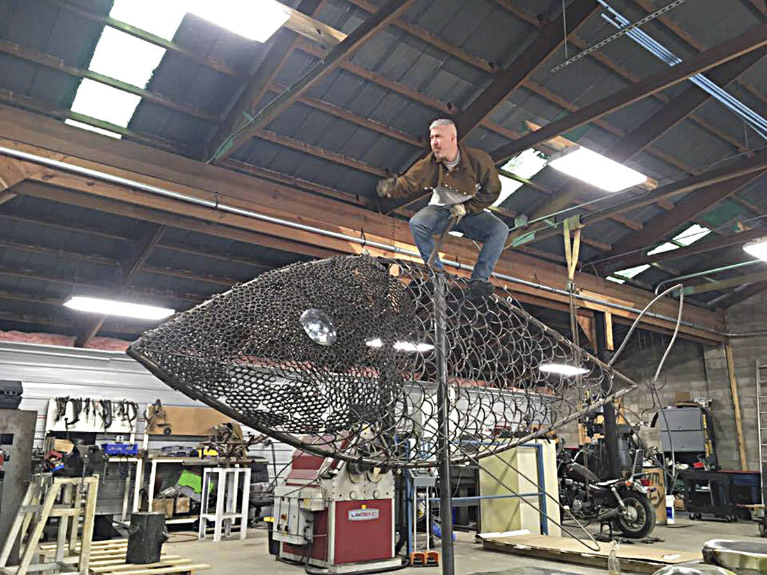 Photo submitted by David Griesmyer Welding artist David Griesmyer, 38, of Malta, Ohio, stands on top of his 20-foot fish that will be displayed this weekend at the Brick Street Arts Bash in Marietta.