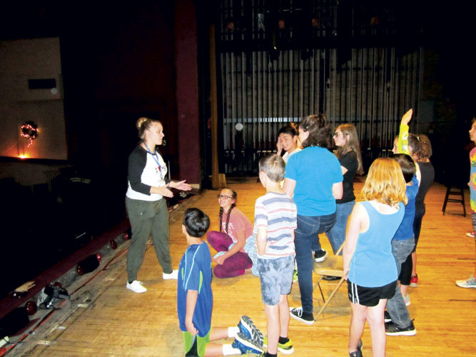 "Photo by Wayne Towner Caroline Clay, at left, a tour director with Missoula Children's Theatre, works with a group of local students on the Smoot Theatre stage in preparation for two performances of the show ""Peter and Wendy"" on Saturday."