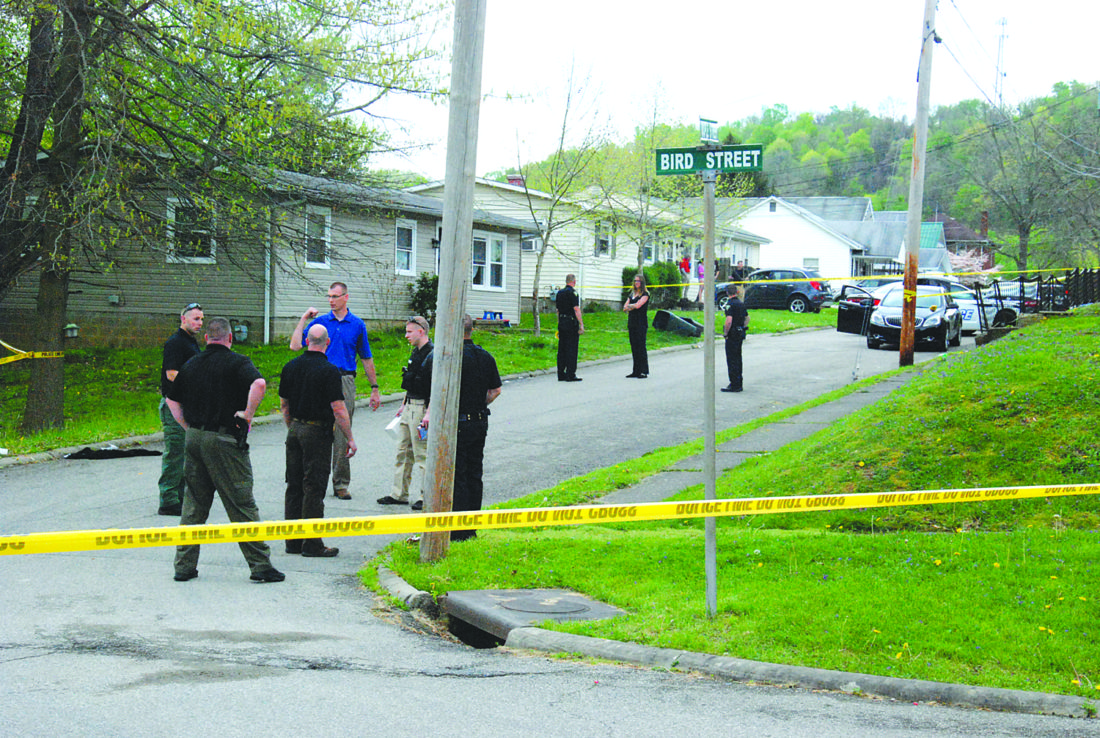 Photo by Evan Bevins Parkersburg Police officers are shown in front of 512A Maple St., where a 26-year-old man was shot in the back Wednesday afternoon.