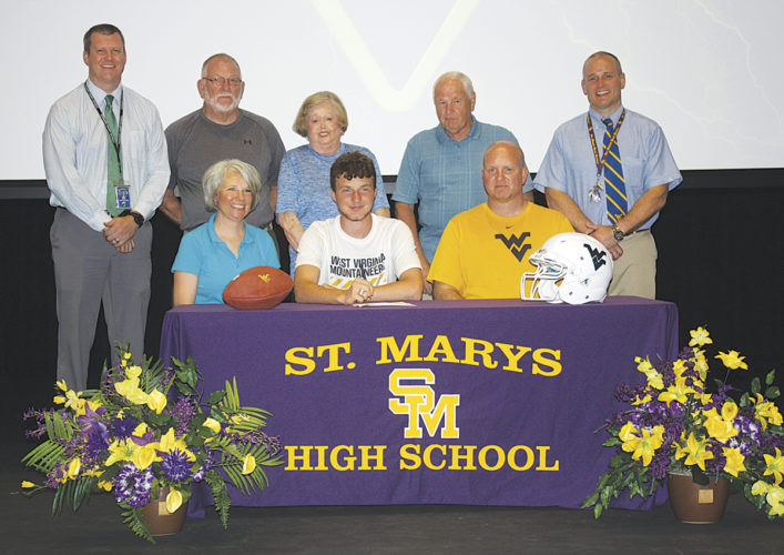 St. Marys' Will Billeter signs on the dotted line to play football for West Virginia University as a preferred walk-on next season. Seated next to the signee is mother Jill Billeter, at left, and father Brad Billeter on the right. Photo by Joe Albright.