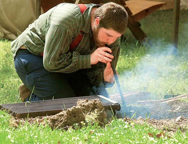 File Photo Kody Reed of Grafton blows into a pit to start a fire during a previous Rendezvous on the River on Blennerhassett Island Historical State Park. This year's Rendezvous began Wednesday and runs through Saturday, with another event planned in June.
