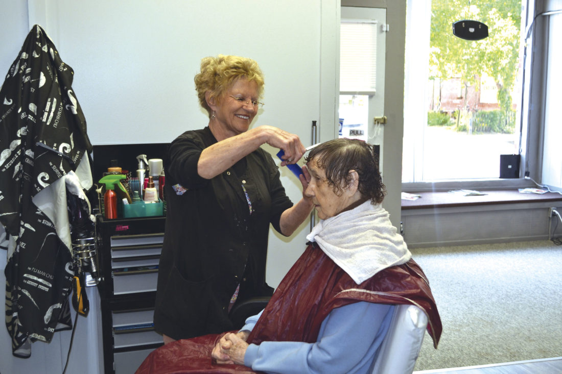 Photo by Erin O'Neill Carolyn Hurst, owner of Classic Cuts, gives customer ImaLee Yoho a perm at the new shop at 118 Maple St.