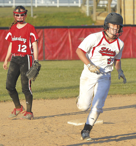 Hurricane's Jayme Bailey rounds second base after hitting a game-ending home run in an 11-1 Class AAA regional victory over Parkersburg Tuesday. Parkersburg's Maddi Leggett (12) looks on. Photo courtesy of Chris Dorst, The Gazette-Mail.