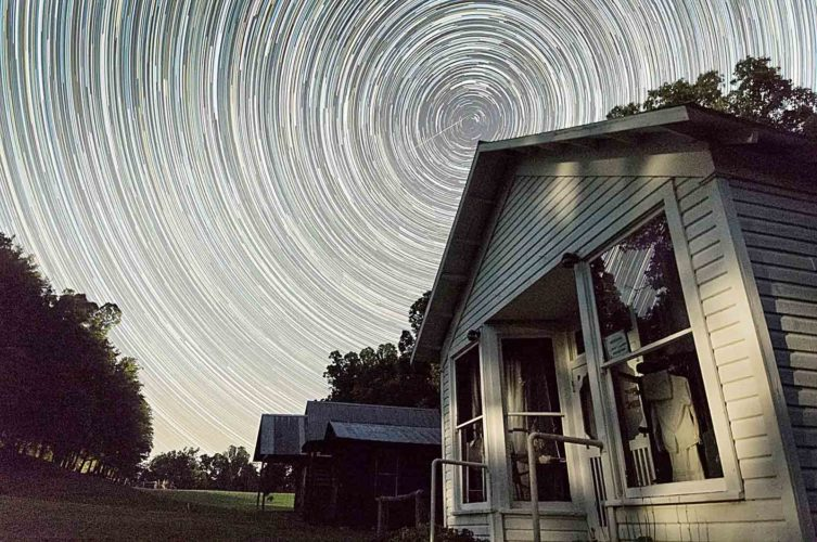 Photo by Jesse Thornton, provided by Mid-Ohio Valley Regional Council A time-lapse image of the night sky is shown over the Calhoun Historic Village in Calhoun Park. The park will welcome astronomers for a stargazing event this weekend that takes advantage of the dark skies in the area.