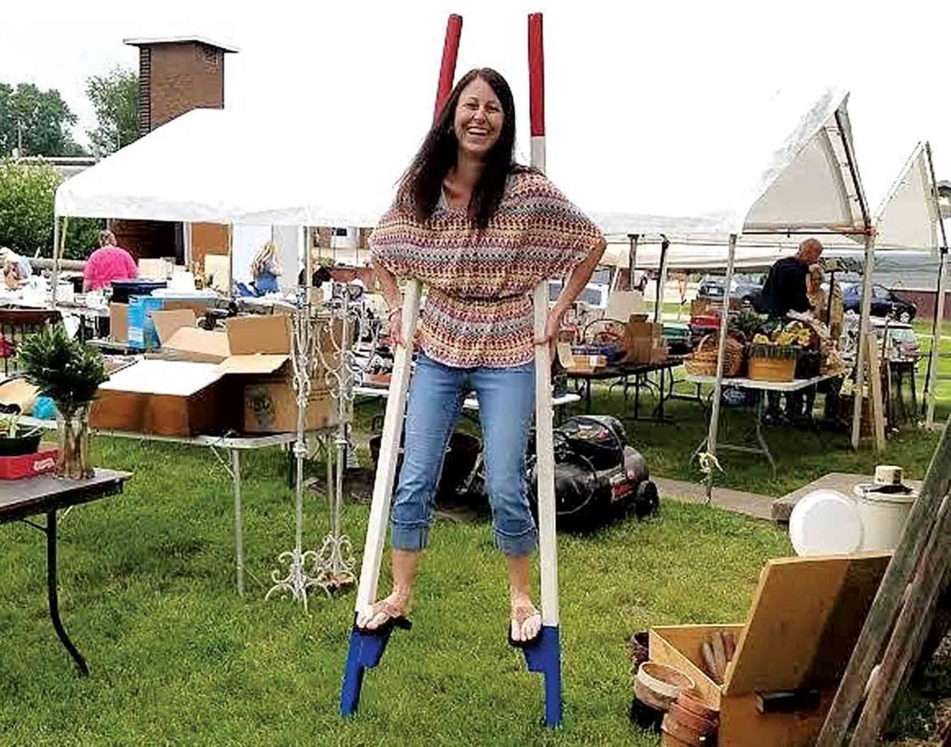 "Photo Provided Tina Merrill is shown ""trying out"" a set of stilts at the Raise the Roof yard sale on May 20 to benefit the Wood County Historical and Preservation Society and a new roof at the Phelps-Tavenner Research Center on Camden Avenue."