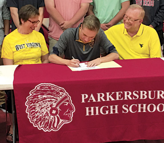 Photo by Joe Albright  Parkersburg High swimmer Nathan Burd, flanked by his parents Leone (Ohnoutka) Burd (left) and Charlie Burd (right), signs on the dotted line Wednesday to swim for West Virginia University the next four years inside PHS Memorial Fieldhouse.