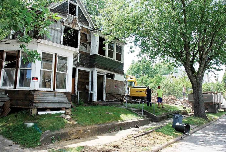 File Photo The vacant house that once stood at 1004 Virginia Ave. in Parkersburg is shown in August 2016 as employees of West Virginia Roofing tear down a neighboring structure. The company received approval from the Municipal Planning Commission Friday to have the property rezoned so its new offices can be built there. The matter now goes to Parkersburg City Council.