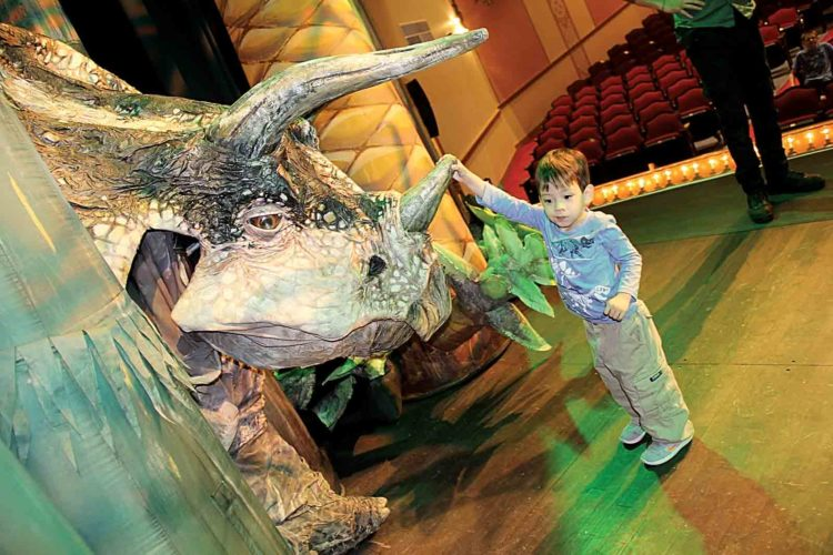 Photo by Janelle Patterson Jake Sommer, 3, of Marietta, meets a Triceratops at Peoples Bank Theatre Friday.
