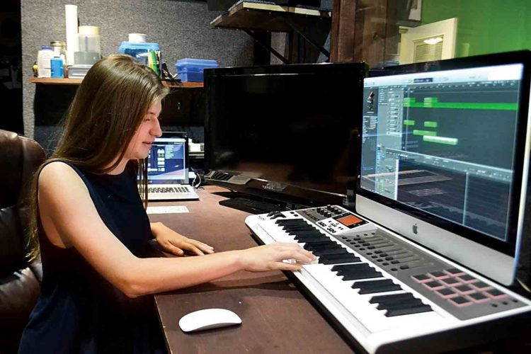 Photo by Peyton Neely Marietta High School sophomore Grace Arnold plays the piano while learning how to produce music at the MOV2GO studios in Little Hocking on Friday.