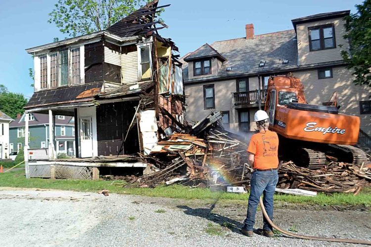 Photo by Peyton Neely Workers with Ken Strahler Masonry demolish the house at 506 Front St. early Thursday morning.