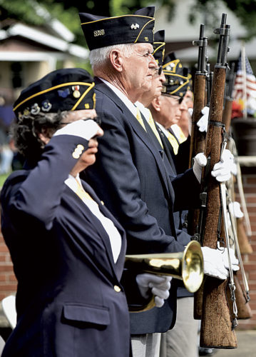 """File Photo Stan Null stands at attention along with the American Legion Post 15 color guard during last year's Memorial Day services at City Park in Parkersburg. Mariann Bennett salutes while holding the bugle for """"Taps."""""""